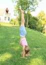Girl training handstand exercising little kid barefoot on green grass of village meadow Royalty Free Stock Image