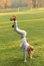 Girl training handstand exercising little kid in grey clothes and brown shoes on green grass of football stadion Royalty Free Stock Images