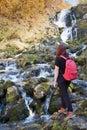 Girl traveler trekker climbs the waterfall stones, active Hiking Royalty Free Stock Photo