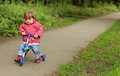 Girl on a tricycle little riding her pathway in park in spring Stock Images