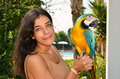 Girl and tropical parrot horizontal photo of a happy young smiling posing with a macaw she is on holiday or vacation Stock Image