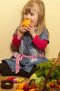 Girl trying to eat an orange little sitting cross legged with the skin on it with fruits and vegetables beside her Royalty Free Stock Photos