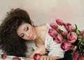 Girl and tulips young lying on the bed surrounded by Royalty Free Stock Photo
