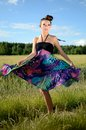 Girl turning around young female model spins charming from poland dynamic photo with colorful dress green fields and blue sky as Royalty Free Stock Image