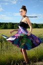 Girl turning around young female model spins charming from poland dynamic photo with colorful dress green fields and blue sky as Stock Photo