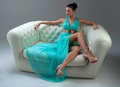Girl in a turquoise dress on sofa lying Royalty Free Stock Image
