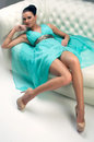 Girl in a turquoise dress on sofa lying Stock Image