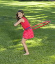 Girl twirling a hula hoop with long brown hair and brown eyes who just lost her two front teeth smiles as she plays with red on Stock Image