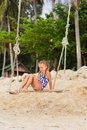Girl with two braids in a bathing suit on a swing on the beach resting tropics Royalty Free Stock Photos