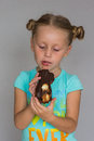 The girl with two plaits biting a chocolate cake Royalty Free Stock Photo