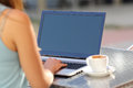 Girl typing on a laptop and showing screen closeup of in restaurant terrace Stock Image