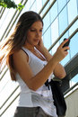 Girl typing sms texting young beautiful brunette on a mobile phone outdoors in a sun with building background Stock Photo