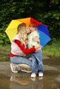 Girl with an umbrella in the rain playing with mom little Stock Photo