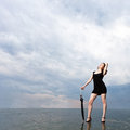 Girl with umbrella stands on the water Royalty Free Stock Photo