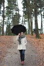 Girl with umbrella walking down the hill on a rainy day Royalty Free Stock Photos