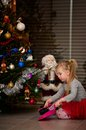 Girl under Christmas tree cleaning needles Royalty Free Stock Photo