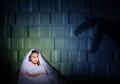 Girl under the covers with a flashlight image of night afraid of ghosts Royalty Free Stock Photos