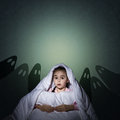 Girl under the covers with a flashlight image of night afraid of ghosts Stock Images