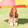 Girl under the red and yellow umbrella little in grey t shirt kneeing a in shadow Stock Images