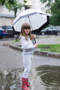 Girl under white umbrella cheerful in the park in a puddle Stock Image
