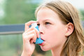 Girl uses an inhaler during an asthma attack Royalty Free Stock Photo
