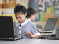 Girl using laptop in class young schoolgirl at desk with boy background Stock Images
