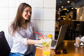 Girl using laptop and drink fresh at cafe Royalty Free Stock Photo