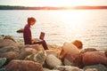 Girl using laptop at sea pretty sunny stone coast Royalty Free Stock Image