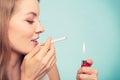 Girl using lighter to light cigarette. Royalty Free Stock Photo