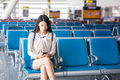 Girl using phone while waiting boarding at airport Royalty Free Stock Photo