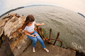 Girl using smart phone sitting on an old mooring young woman broken taken with a fisheye lens image retro vintage filter effect Royalty Free Stock Image