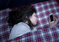 Girl using smartphone in bed Royalty Free Stock Photo