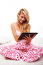 Girl using a tablet on her bed Stock Image