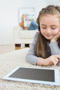 Girl using tablet with her mother reading the newspaper on the couch little happily carpet Royalty Free Stock Photos