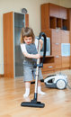 Girl with vacuum cleaner on parque in living room Royalty Free Stock Photos