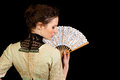 Girl in victorian dress with fan seen from the back a her hands on a black background Stock Photo