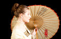 Girl in victorian dress in profile with chinese umbrella a on a black background Stock Photography