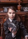 Girl with vintage camera in pin striped suit sat in antique shop holding Stock Photos