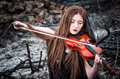 Girl with a violin sitting on the ashes Royalty Free Stock Photos