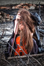 Girl with a violin sitting on the ashes Royalty Free Stock Photography