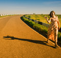 Girl walking along the road sunny day affably waves Royalty Free Stock Photo