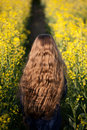 Girl walking away in the rape field Stock Photos