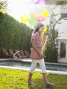 Girl Walking With Balloons By Swimming Pool