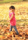 Girl walking barefoot in dead maple leaves barefooted with plaits pink t shirt and blue jeans on autumn Stock Photo