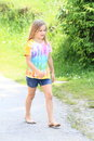Girl walking barefoot little in colorful t shirt and blue shorts on grey asphalt street Royalty Free Stock Image