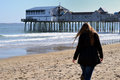 Girl walking at beach old orchard by the pier Stock Images