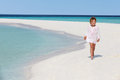 Girl walking on beautiful tropical beach smiling Royalty Free Stock Photography