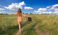 Girl walking in the countryside happy with a retro travelling bag view from back Stock Photography