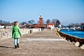 Girl walking on darlowo jetty a five year old alone poland or pier towards the lighthouse Stock Photo