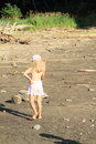 Girl walking on drying ground little barefoot in shorts and cap and holding her back Stock Photography